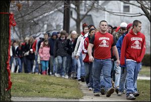 Hundreds of students, along with their parents, walk to Chardon High School in honor of the three students shot and killed on Monday. Classes resume a full schedule on Friday.