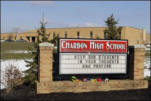 Bouquets of flowers sit on the sign in front of the high school in ChardonTuesday. A gunman opened fire inside the school's cafeteria at the start of the school day Monday, killing three students and injuring two more.