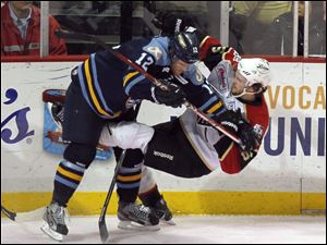 The Walleye's Mike Thomas, left, upends Wheeling's Andrew Hotham. More than 7,000 fans were at the Huntington Center.