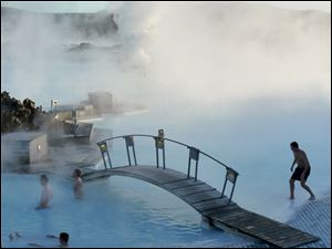 Visitors to Iceland's Blue Lagoon swim in pools of milky-blue, 99-degree geothermal waters.