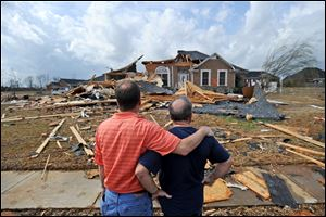 Jerry Vonderhaar, left, comforts Charles Kellogg after severe weather hit the Eagle Point subdivision in Limestone County, Ala. on Friday.
