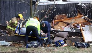 Walton Ky. firefighters rescue a woman who was trapped under debris behind a house Friday in Boone County, Ky.