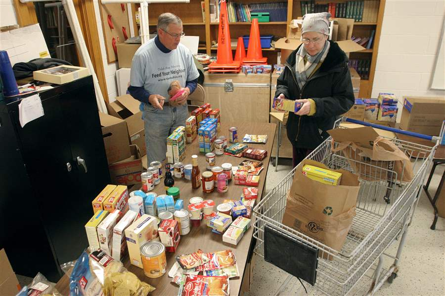 Steve-Drake-Feed-Your-Neighbor-worker-helps-Tammie-Huth-select-food-at-Augsburg-Lutheran-Church