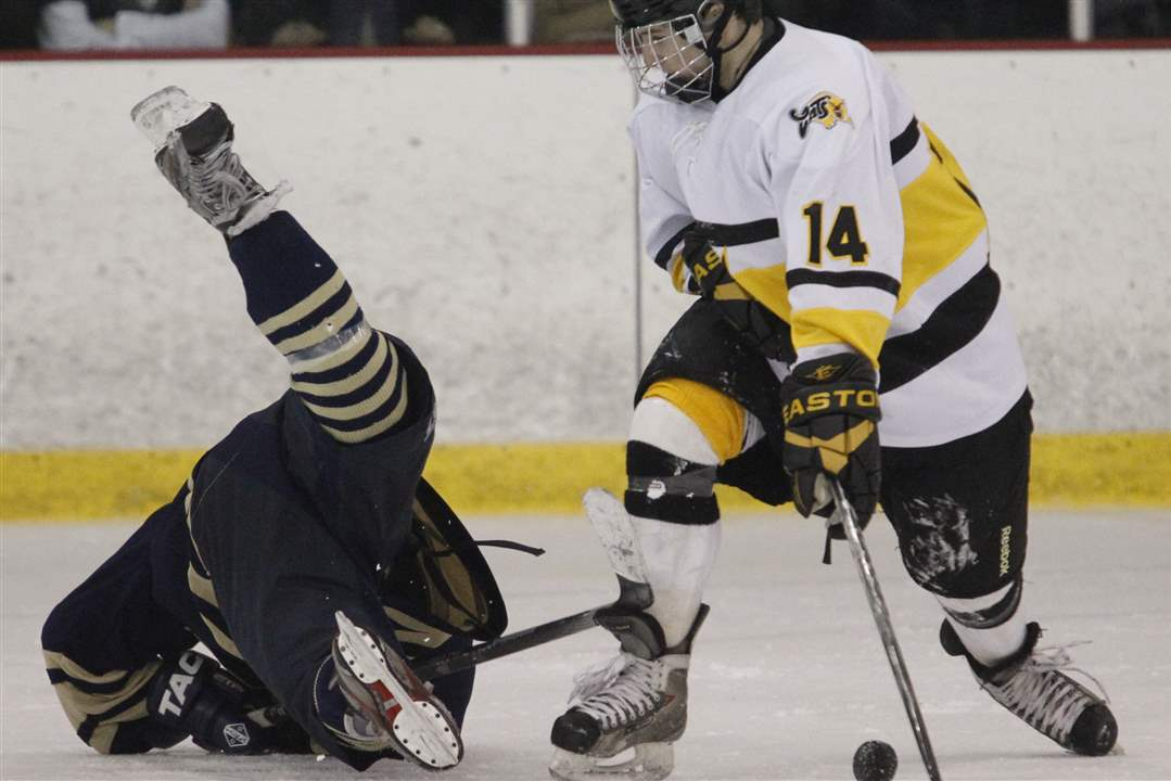 Sylvania-Northview-player-Kooper-Carter-14-steals-the-puck-from-Toledo-St-John-s-Jesuit-player-Austin-Kelly