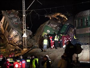 Rescue officials work at the scene where two trains collided in Szczekociny, southern Poland, killing several people and injuring dozens of others, Saturday evening.