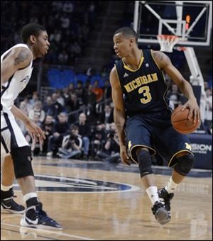 Michigan's Trey Burke (3) looks for room around Penn State's Jermaine Marshall in the second half.