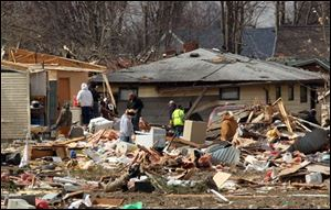Residents search through the debris from Friday's storm in hopes of salvaging items on Sunday in Holton, Ind. A string of violent storms scratched away small towns in Indiana and cut off rural communities in Kentucky as an early-season tornado outbreak struck on Friday.