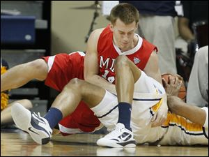 University of Toledo guard Curtis Dennis (33) battles Miami guard Brian Sullivan (14)  for a loose ball.