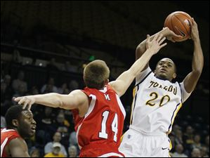 University of Toledo guard Julius Brown (20) takes a shot against  Miami guard Brian Sullivan (14).