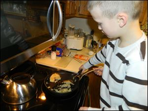 Ben Tucker flips the rice pancakes he and his mother, Lisa, created for the Uncle Ben's contest. The Highland Elementary student is among 500 finalists in the contest. The recipe called for cooked white rice, two teaspoons milk, two eggs, a dash of salt, and a handful of fruit.
