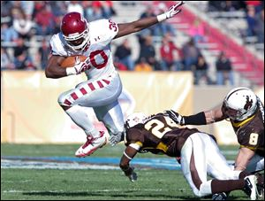Temple running back Bernard Pierce (30) leaps over Wyoming defensive back Kenny Browder (24) and linebacker Brian Hendricks (8) in the 2011 New Mexico Bowl in Albuquerque, N.M.