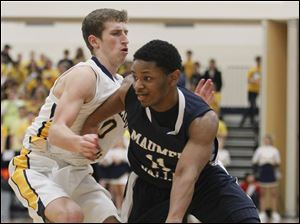 Maumee Valley's Julius Turner (11) drives to the basket against Toledo Christian's Josh Winzeler (10) during the Division IV boys district championship.
