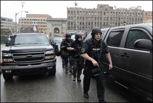 Police in SWAT gear make their way up the street to the Western Psychiatric Institute. Three University of Pittsburgh police officers traded fire with the shooter.