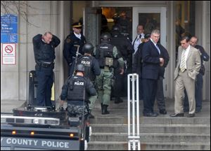 Police walk through the main entrance to Western Psychiatric Institute. Pittsburgh Mayor Luke Ravenstahl praised the public safety employees as well as the institute's staff.