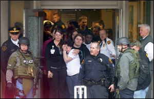 People crowd the doorway at the main entrance to the facility as they wait to be evacuated from the scene. The UPMC hospitals were put on alert at 1:58 p.m. that a gunman had entered the building.