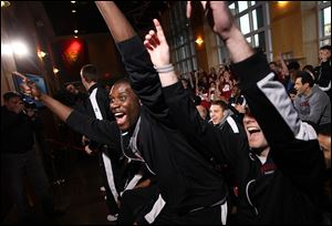 Harvard's Kyle Casey, left, and Andrew Van Nest react to their draw to play Vanderbilt in the NCAA college basketball tournament during a selection show party on Sunday in Cambridge, Mass.