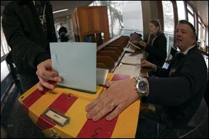 A man casts his vote in Carouge, Switzerland, Sunday. Swiss polls closed Sunday on several national referendums, including one to raise the minimum holiday from four weeks to six weeks, the standard used in Germany, Italy, Russia and many other European nations.