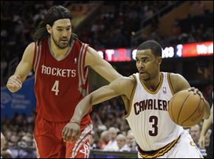The Cavaliers' Ramon Sessions (3) drives past the Rockets' Luis Scola (4) in the fourth quarter.