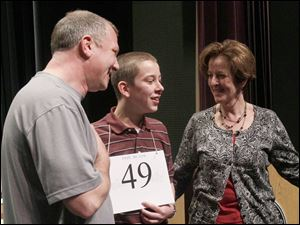 Spencer Hipsher, 13, is flanked by his proud parents, Ron and Lynn Hipsher, after he spelled lenitive correctly to win the spelling bee.