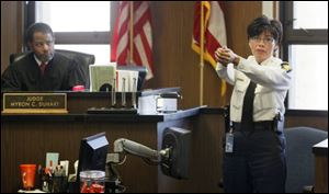 "Deputy Chief Diana Ruiz-Krause demonstrates how Sgt. Gloria Burks pointed a gun at her in a ""high ready"" position, during her testimony in Burks trial in Lucas County Common Pleas Court in Toledo, Wednesday, March 14, 2012. Looking on is Judge Myron Duhart. Burks is on trial for shooting fellow Sgt. Jeff Bechtel at the Scott Park police station. Deputy Chief Ruiz-Krause encountered Burks just after she shot Sgt. Bechtel at the station."
