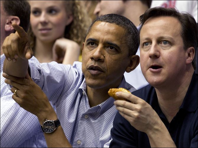 Obama, Cameron show game faces  President Obama guides British Prime Minister David Cameron's view of the action on the basketball court as Mississippi Valley State battles Western Kentucky in the first round of the NCAA tourney at the University of Dayton.