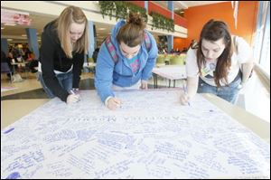 Courtney Brecher, left, a junior from Cleveland, Lucy Sherman, center, a freshman from Vandalia, and Ariel Jones, right, a senior from Sylvania, sign memory boards that are set up in the BGSU student union for people to leave thoughts and condolences for the families of the three sorority girls killed by a wrong-way driver and for the two girls who survived the crash.