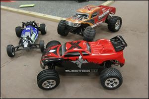 From left to right:  Boost Buggy, Ruckus Monster Truck, back, Circuit Stadium Truck, front, at HobbyTown USA. Pieces from remote control cars like these were used to create the bomb that blew up under Erik Chappell's Volvo.