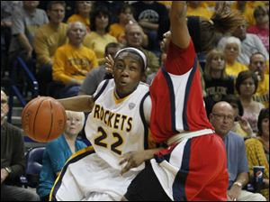 UT's Andola Dortch drives around UDM's Shareta Brown.