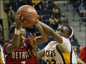 UDM's #1, Jalesa Jones and UT's #22 Andola Dortch reach for a loose ball.