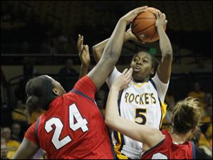 UT's Janelle Reed-Lewis splits UDM defenders Shareta Brown, left, and Megan Hatter.