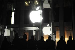 People gather Friday morning outside an Apple retail store on Fifth Avenue in the Manhattan borough of New York as they wait for the 8 a.m. local time release of the new iPad tablet.