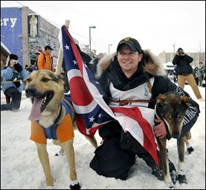 Matt Failor, a Mansfield native and Ohio State graduate, prepares for the start of the Iditarod while holding an Ohio flag. his father, Tim, graduated from Rossford High School, and his mother, Cheryl, graduated from Notre Dame Academy.