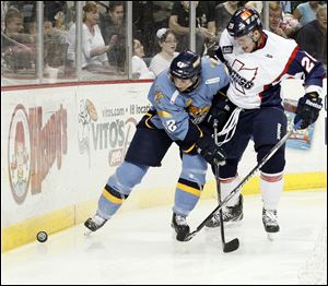 The Walleye's Derek Brochu, left, and Kalamazoo's Joe Tolles fight for the puck Sunday afternoon in Toledo.