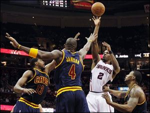 The Hawks' Joe Johnson (2) shoots while defended by the Cavaliers' Tristan Thompson (13), Antawn Jamison (4), and Alonzo Gee.