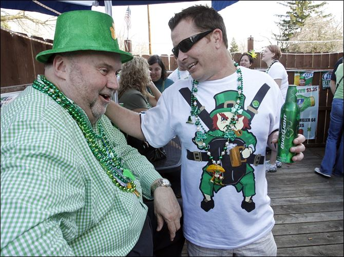 St. Patrick's Day draws family to  favorite local spot Paul Gunner, left, jokes with his nephew Charlie Hendley of Belleville, Mich., as the extended Gunner family reunite for their 45th straight year at OB's Bar & Grill. Mr. Gunner has been spending St. Patrick's Day at the bar since he was old enough to drink beer.