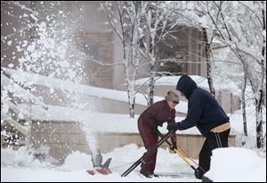 Two Flagstaff, Ariz., residents try to clear their sidewalk even as snow continues to fall. A reporting service said 12 to 18 inches fell on the city Sunday, and a hard freeze made roads extremely slippery.