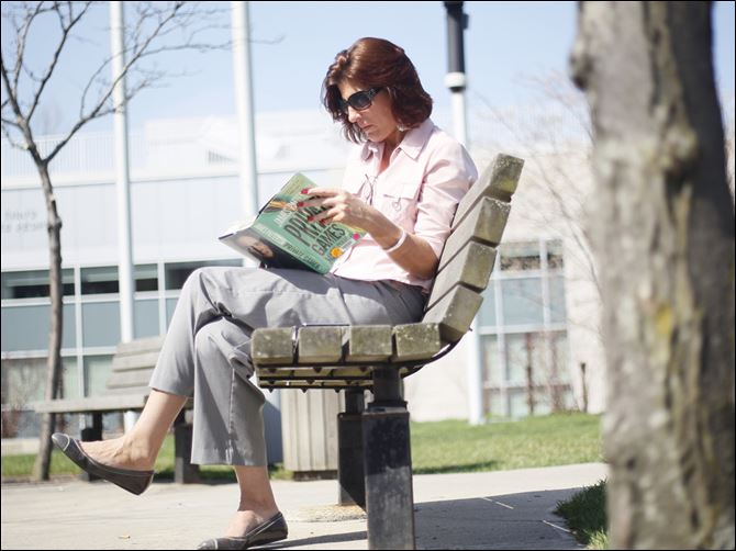 read outside library Beth Blake of Maumee takes a break from the Juvenile Justice Center to read outside the downtown library.