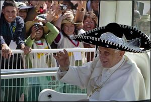 Pope Benedict XVI good-naturedly donned a sombrero that someone passed to him as he rode in his Popemobile Sunday. The Pontiff celebrated Mass before a crowd of 350,000 people.