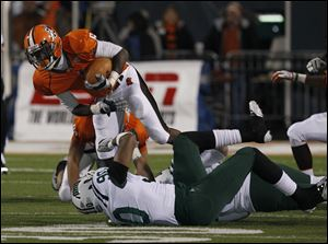 Ohio defensive end  Tremayne Scott, 90, trips up Bowling Green's Anthon Samuel, 6, during a game at Bowling Green.