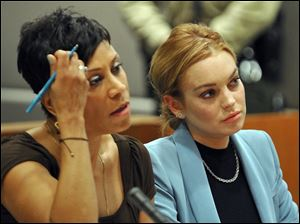 Lindsay Lohan, right, sits with her attorney Shawn Chapman Holley during a progress report on her probation for theft charges at Los Angeles Superior Court Thursday.