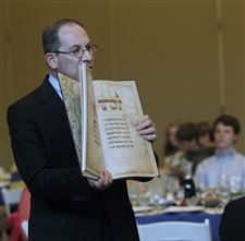 Rabbi-Sam-Weinstein-shows-an-ornate-haggadah