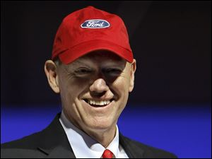 "Ford Motor Co. President and Chief Executive Officer Alan Mulally dons a cap bearing the Ford ""blue oval"" as he talks about Ford's progress during the economic recession at the Washington Auto Show."