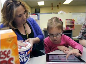 Lauren Miller, speech-and-language pathologist, helps Joselyn 'Jo' Johns, 6, pick a snack during kindergarten at Fort Meigs Elementary School. She began using the device earlier this month.