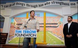 Tim Tebow speaks as his foundation opens the first Timmy's Playroom, for children battling life-threatening illness, in Jacksonville, Fla. Erik Dallenback, right, is the foundation's executive director.