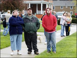 L-R- Kristen, Jeff, and Cody Hoffmann watch firefighters extinguish a fire at St. Rose Church in Perrysburg, Tuesday, April 3, 2012.  The fire was reportedly caused by a lightning strike.