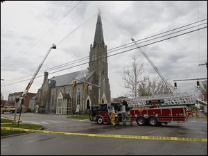 Firefighters extinguish a fire at St. Rose Church in Perrysburg, Tuesday, April 3, 2012.  The fire was reportedly caused by a lightning strike.