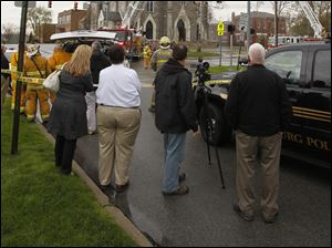 Spectators watch as firefighters extinguish a fire at St. Rose Church in Perrysburg, Tuesday, April 3, 2012.  The fire was reportedly causde by a lightning strike.
