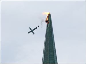 The cross on  St. Rose Church in Perrysburg, topples after the church was struck by lightning Tuesday.