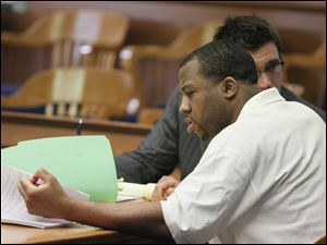 Anthony Belton looks through papers as a defense witness offers testimony. Behind him is defense attorney Neil McElroy. Belton faces a sentence of life in prison or death in the 2008 shooting death of Matthew Dugan, a clerk at a former BP gas station.