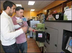 Sales and marketing director Chris Markho, left, shows customer Justin Lusher how to prepare a machine to make cigarettes at the RYO Filling Station at Tobacco Haven on Spring Valley Drive in Holland.